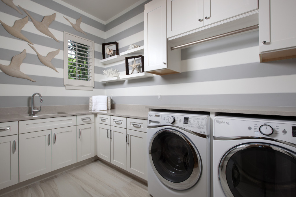 The laundry room of this custom home features floating shelves to display accessories